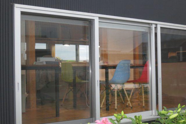 ガラス越しに見える打ち合わせテーブルとクール暖パネル
